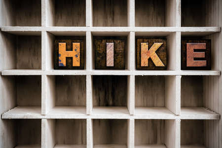 hitch hiker: The word HIKE written in vintage ink stained wooden letterpress type in a partitioned printers drawer. Stock Photo