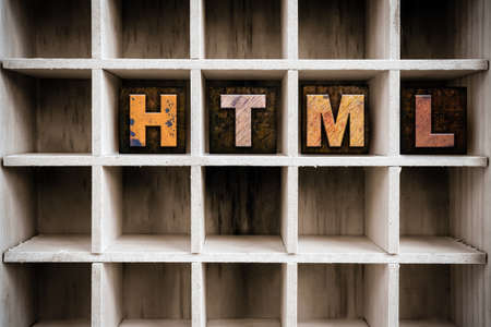 html: The word HTML written in vintage ink stained wooden letterpress type in a partitioned printers drawer. Stock Photo