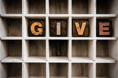 dispense: The word GIVE written in vintage ink stained wooden letterpress type in a partitioned printers drawer. Stock Photo