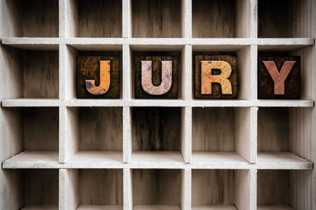 jurors: The word JURY written in vintage ink stained wooden letterpress type in a partitioned printers drawer. Stock Photo