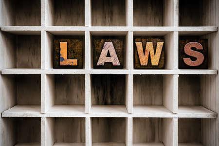 """edicto: La palabra """"ley"""" escrita con tinta vendimia manchado tipo de tipografía de madera en el cajón de una impresora con particiones."""