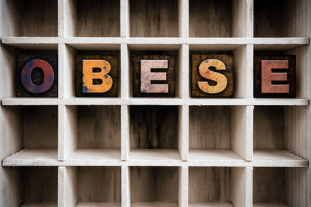 childhood obesity: The word OBESE written in vintage ink stained wooden letterpress type in a partitioned printers drawer.