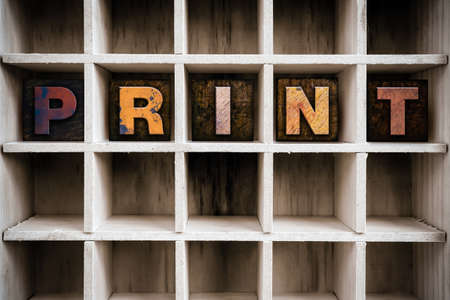 lithograph: The word PRINT written in vintage ink stained wooden letterpress type in a partitioned printers drawer. Stock Photo