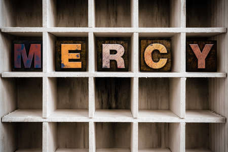 The word MERCY written in vintage ink stained wooden letterpress type in a partitioned printers drawer. Stock Photo