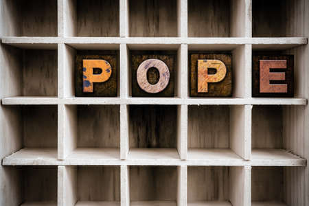 pontiff: The word POPE written in vintage ink stained wooden letterpress type in a partitioned printers drawer.