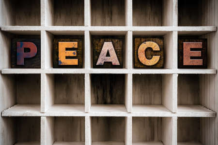 ceasefire: The word PEACE written in vintage ink stained wooden letterpress type in a partitioned printers drawer.