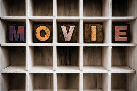 letterpress letters: The word MOVIE written in vintage ink stained wooden letterpress type in a partitioned printers drawer. Stock Photo