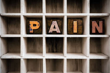 pain killers: The word PAIN written in vintage ink stained wooden letterpress type in a partitioned printers drawer.