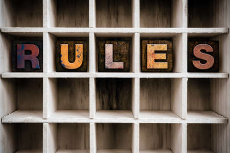 precedent: The word RULES written in vintage ink stained wooden letterpress type in a partitioned printers drawer. Stock Photo
