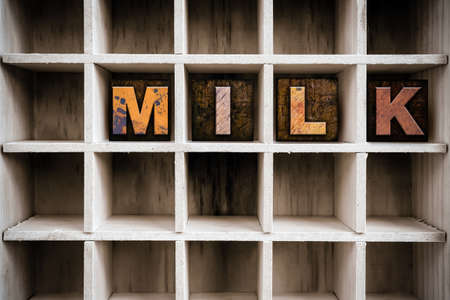 letter blocks: The word MILK written in vintage ink stained wooden letterpress type in a partitioned printers drawer.
