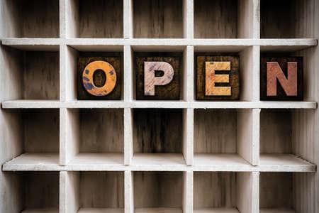 """Het woord """"OPEN"""" geschreven in vintage inkt gekleurde houten letterpress type in een lade van een partitielade printer."""