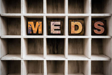 meds: The word MEDS written in vintage ink stained wooden letterpress type in a partitioned printers drawer.