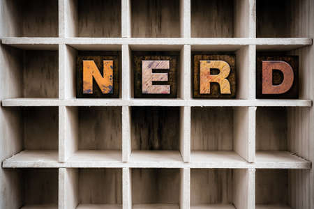 dweeb: The word NERD written in vintage ink stained wooden letterpress type in a partitioned printers drawer. Stock Photo