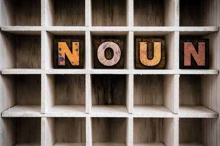 noun: The word NOUN written in vintage ink stained wooden letterpress type in a partitioned printers drawer. Stock Photo