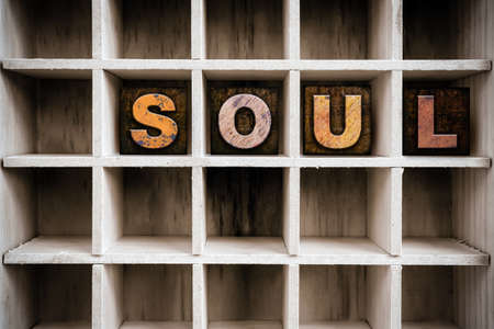 soulful: The word SOUL written in vintage ink stained wooden letterpress type in a partitioned printers drawer.