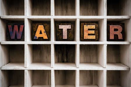 water stained: The word WATER written in vintage ink stained wooden letterpress type in a partitioned printers drawer. Stock Photo