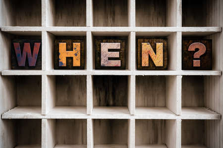when: The word WHEN written in vintage ink stained wooden letterpress type in a partitioned printers drawer.