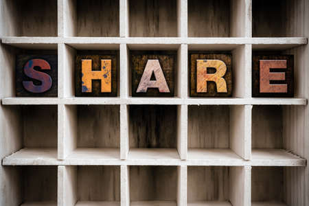 shared sharing: The word SHARE written in vintage ink stained wooden letterpress type in a partitioned printers drawer. Stock Photo