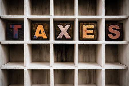 custom cabinet: The word TAXES written in vintage ink stained wooden letterpress type in a partitioned printers drawer. Stock Photo