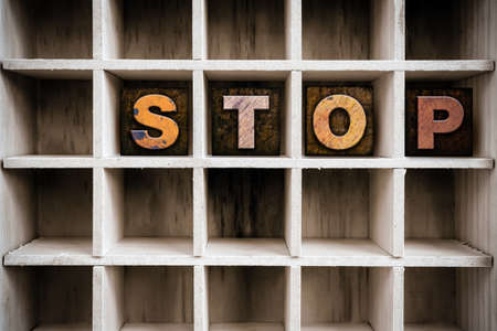 conclude: The word STOP written in vintage ink stained wooden letterpress type in a partitioned printers drawer.