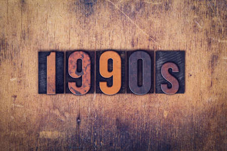 decade: The word 1990s written in dirty vintage letterpress type on a aged wooden background.