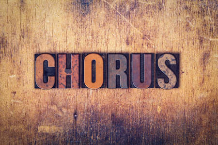 harmonize: The word Chorus written in dirty vintage letterpress type on a aged wooden background.