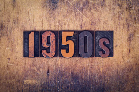 fifties: The word 1950s written in dirty vintage letterpress type on a aged wooden background. Stock Photo