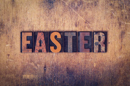 The word Easter written in dirty vintage letterpress type on a aged wooden background. Stock Photo