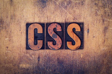 The word CSS written in dirty vintage letterpress type on a aged wooden background. Stock Photo