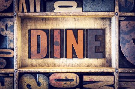 """Het woord """"dineren"""" geschreven in vintage houten boekdruk type."""