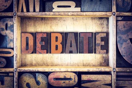 """Het woord """"debat"""" geschreven in vintage houten boekdruk type."""