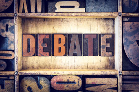 """The word """"Debate"""" written in vintage wooden letterpress type."""