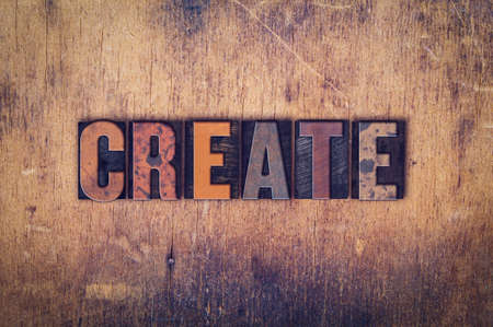 devise: The word Create written in dirty vintage letterpress type on a aged wooden background.