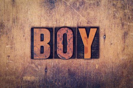 """Das Wort """"Boy"""" in schmutzige Weinlesehhhochhdrucktypen auf einem gealterten hölzernen Hintergrund geschrieben. Standard-Bild"""