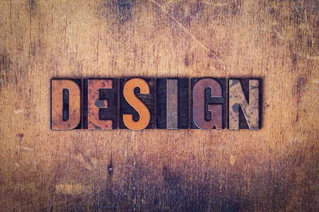 The word Design written in dirty vintage letterpress type on a aged wooden background.