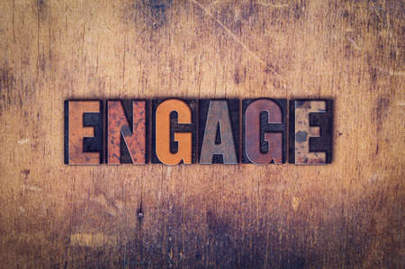 to partake: The word Engage written in dirty vintage letterpress type on a aged wooden background. Stock Photo