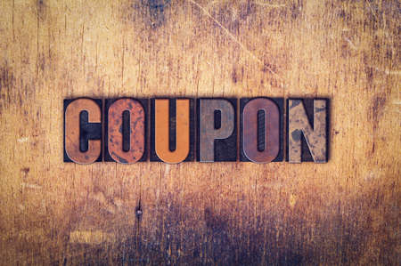 """Het woord """"Coupon"""" geschreven in vuile vintage boekdruk type op een oude houten achtergrond."""