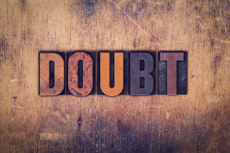 skepticism: The word Doubt written in dirty vintage letterpress type on a aged wooden background. Stock Photo