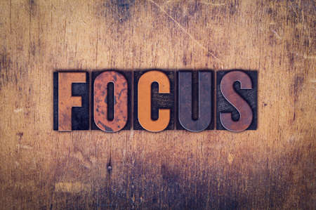 The word Focus written in dirty vintage letterpress type on a aged wooden background.