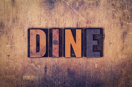 """Het woord """"Dineren"""" geschreven in vuile vintage boekdruk type op een oude houten achtergrond."""