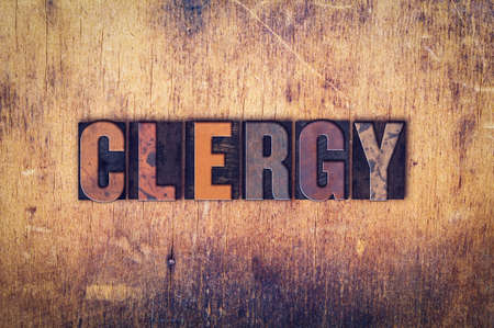 clergy: The word Clergy written in dirty vintage letterpress type on a aged wooden background.