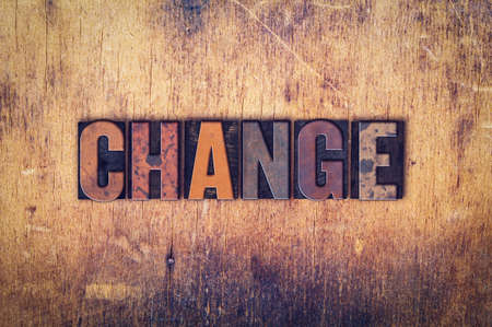 The word Change written in dirty vintage letterpress type on a aged wooden background.
