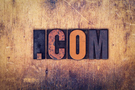 dot com: The word Dot Com written in dirty vintage letterpress type on a aged wooden background.