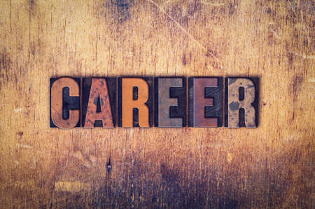 The word Career written in dirty vintage letterpress type on a aged wooden background. Imagens