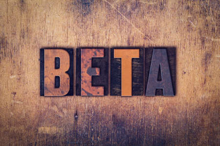 """The word """"Beta"""" written in dirty vintage letterpress type on a aged wooden background."""