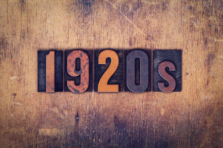 The word 1920s written in dirty vintage letterpress type on a aged wooden background.