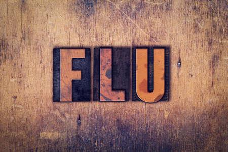 flu shots: The word Flu written in dirty vintage letterpress type on a aged wooden background. Stock Photo