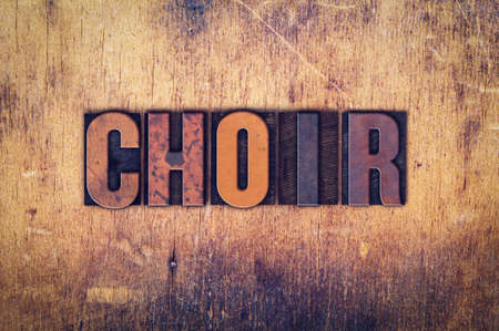 harmonize: The word Choir written in dirty vintage letterpress type on a aged wooden background.