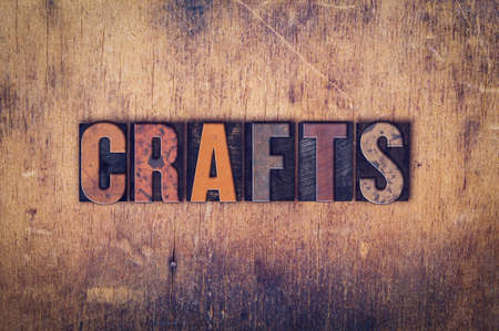 """The word """"Crafts"""" written in dirty vintage letterpress type on a aged wooden background."""