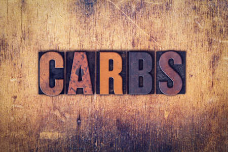 carbs: The word Carbs written in dirty vintage letterpress type on a aged wooden background.